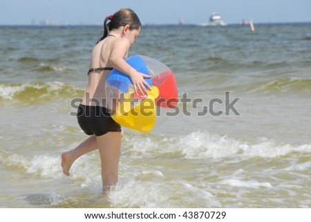 Young girl playing with beach ball in surf