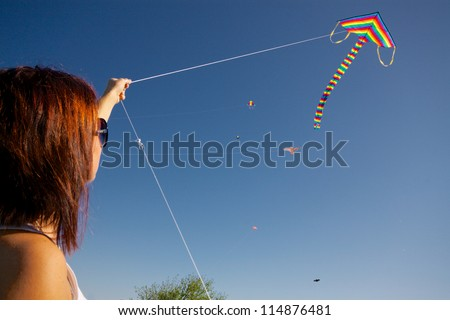 Young girl playing with colorful flying kite on sunny autumn day