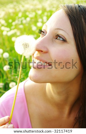young girl playing with dandelion - stock photo