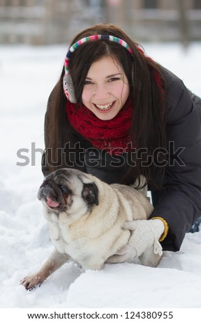 Young girl playing with funny pug puppy in snow