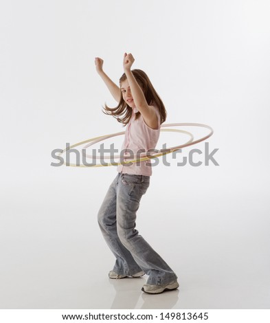 Young girl playing with hula hoops - stock photo