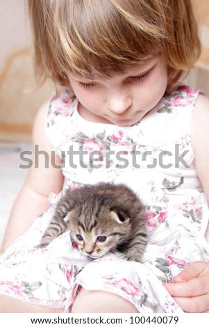 young girl playing with kitten at home - stock photo