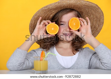 Young girl playing with oranges and drinking orange juice - stock photo