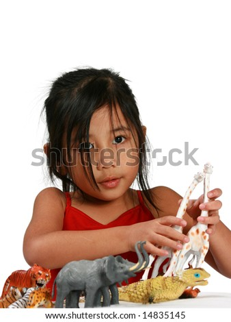 Young girl playing with toy animals - stock photo