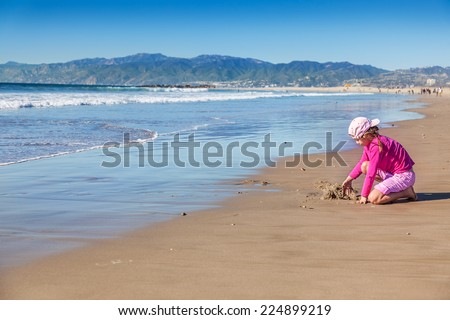 Young girl plays at water's edge on a sunny winter day at Venice Beach, California - stock photo