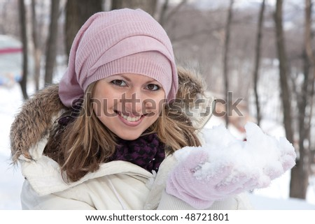 Young girl plays with snow