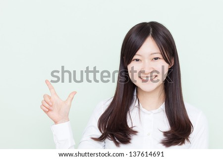 young girl pointing copy space against pale green background