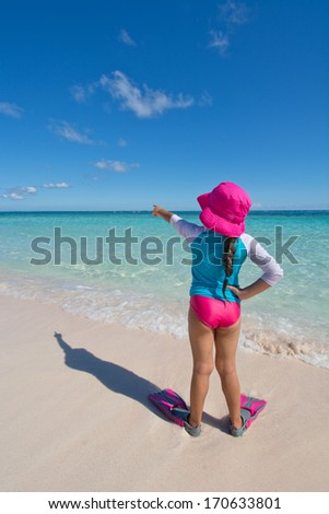 Young Girl Pointing out to Sea on Beach