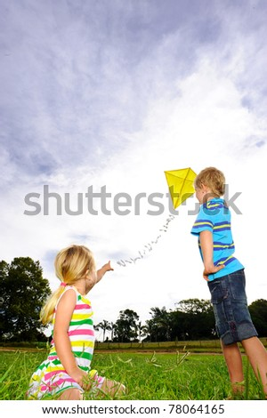 Young girl points at her yellow kite flying high in the sky - stock photo