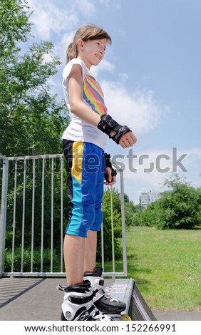Young girl poised at the top of a skating ramp standing in her rollerblades and wrist guards preparing herself to jump while enjoying the summer sunshine roller skating - stock photo