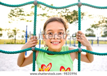 Young girl poking head through climbing rope activity using it as frame. - stock photo