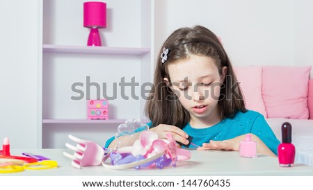 Young girl polishing her nails - stock photo
