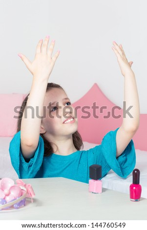 Young girl polishing her nails and showing her mom how beautiful they are - stock photo