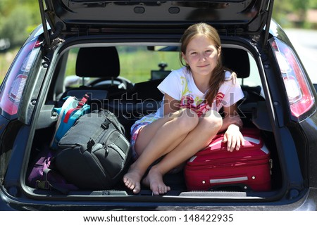 young  girl portrait at the car trunk  - stock photo