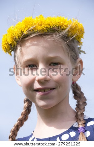 young girl portrait in yellow dandelion garland on blue sky background - stock photo