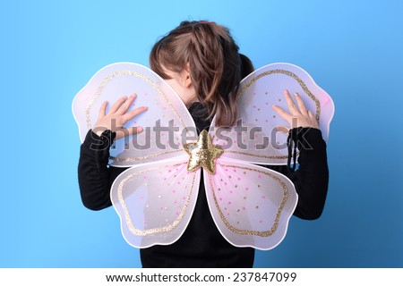 Young girl portrait with butterfly costume against blue background.  - stock photo