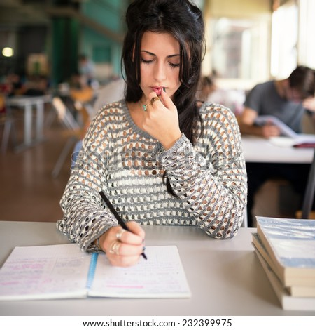 Young girl portrait wwriting on note book and studying in college library.  - stock photo