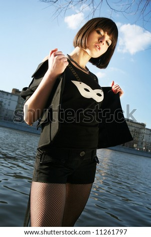 Young girl posing in fancy clothes by the river. Moscow city background - stock photo