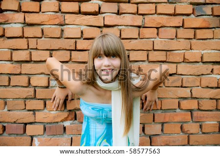 Young girl posing in front of the wall - stock photo