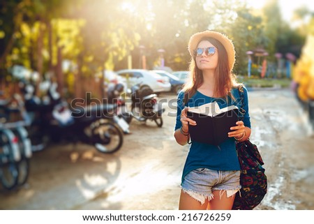 Young girl posing in the street with a notebook - stock photo