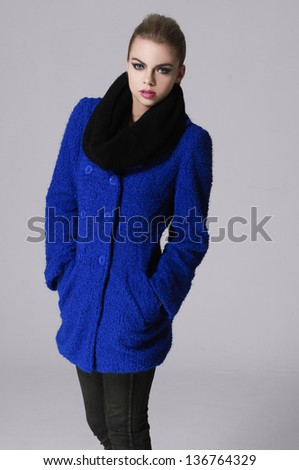 young girl posing over gray, model in a blue coat posing - stock photo