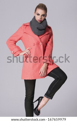 young girl posing over gray, model in a coat with scarf - stock photo