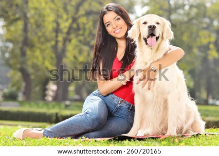 Young girl posing with her dog in a park - stock photo