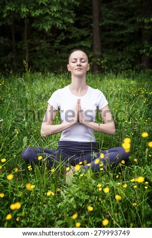 Young girl practicing and meditating in a forest - stock photo