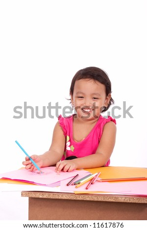 young girl practicing how to write using colored pencil
