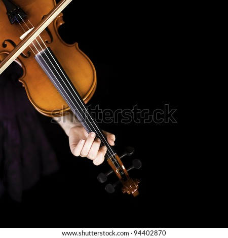 Young girl practicing the violin. Over black background.