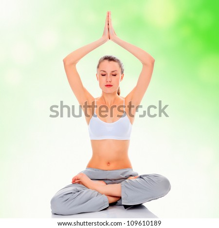 young girl practicing yoga, green blurred background - stock photo
