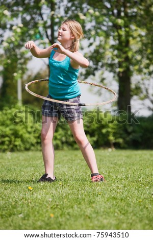 Young girl practising a hula hoop - stock photo