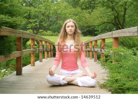 Young girl practising yoga in the park on sunny day - stock photo