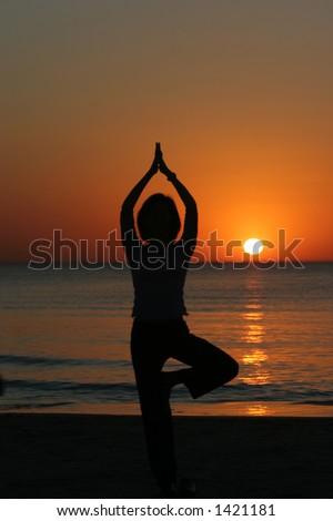 Young Girl preforms Yoga with Setting Sun - stock photo
