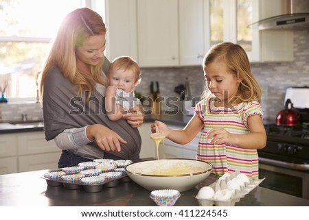 Young girl preparing cake mix in kitchen, mum showing baby - stock photo