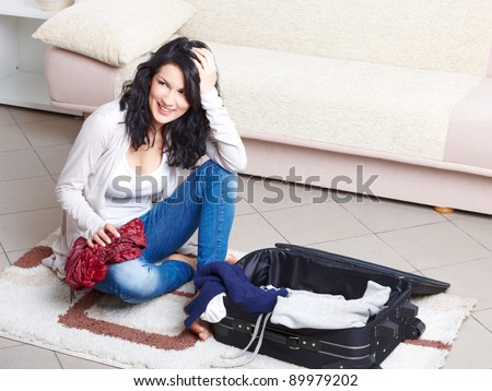 Young girl preparing her luggage before travel. She is in doubt of what to pack - stock photo