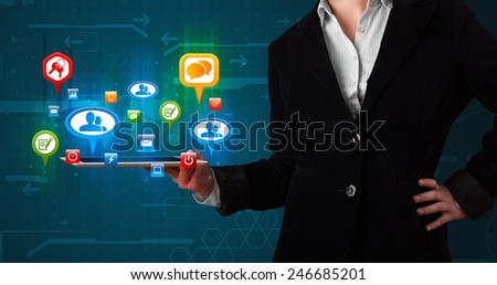 Young girl presenting a tablet with colorful social icons and signs - stock photo