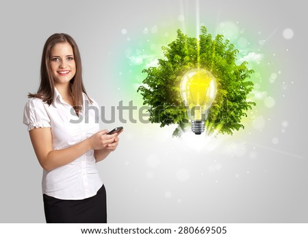 Young girl presenting idea light bulb with green tree concept - stock photo