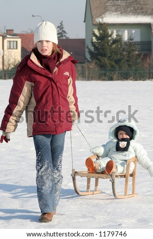 Young girl pulling a baby in sled - stock photo