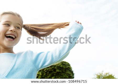 Young girl pulling her ponytails up in the air while playing in the park. - stock photo