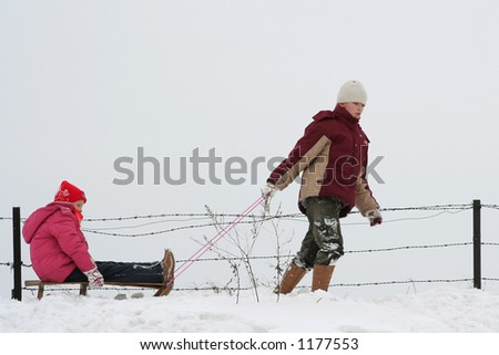 Young girl pulling her younger sister in sled - stock photo