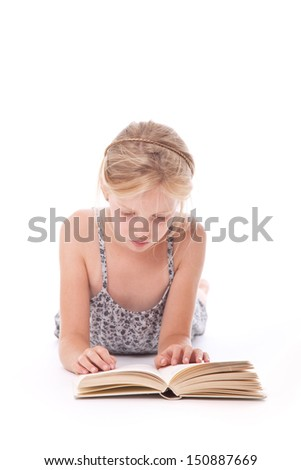 young girl reading a book against white background lying down on floor of studio - stock photo
