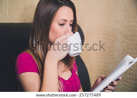 Young girl reading a book and drinking coffee - stock photo