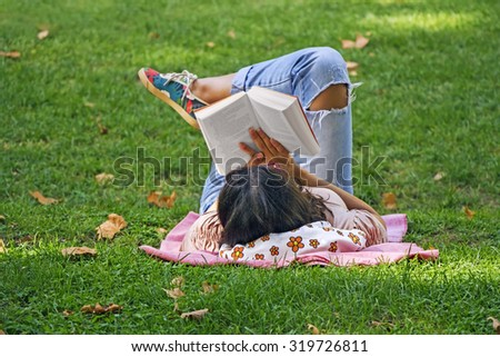 Young girl reading a book lying in the grass in the park - stock photo