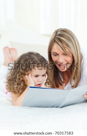 Young girl reading a book with her grandmother - stock photo