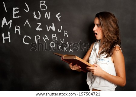 young girl reading a book with letters flying away