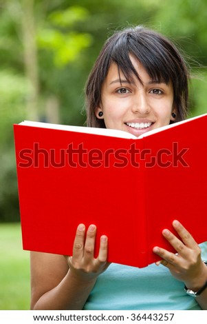 Young girl reading a red book outdoors