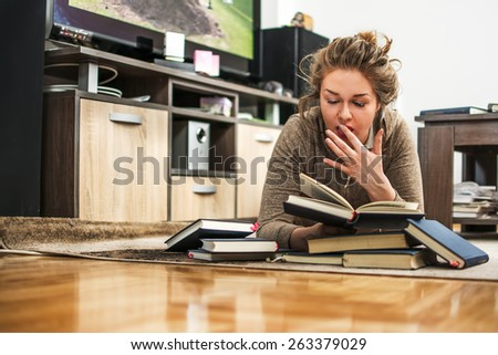 Young girl reading and yawning. - stock photo