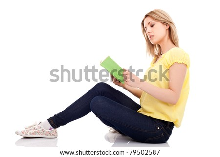 young girl reading book and siting on floor, isolated on white background - stock photo