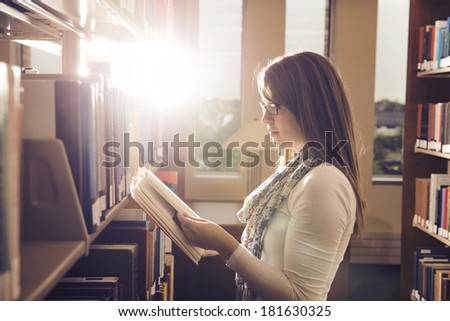 Young girl reading book at library over beautiful sunshine - stock photo